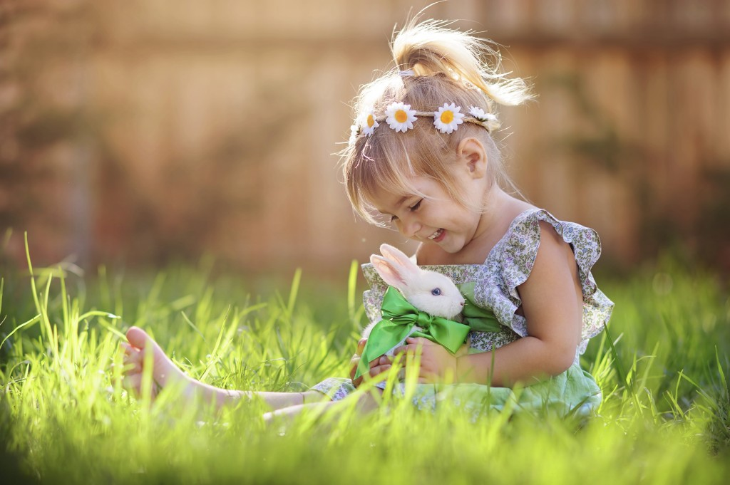 Young girl laughing and smiling at a rabbit